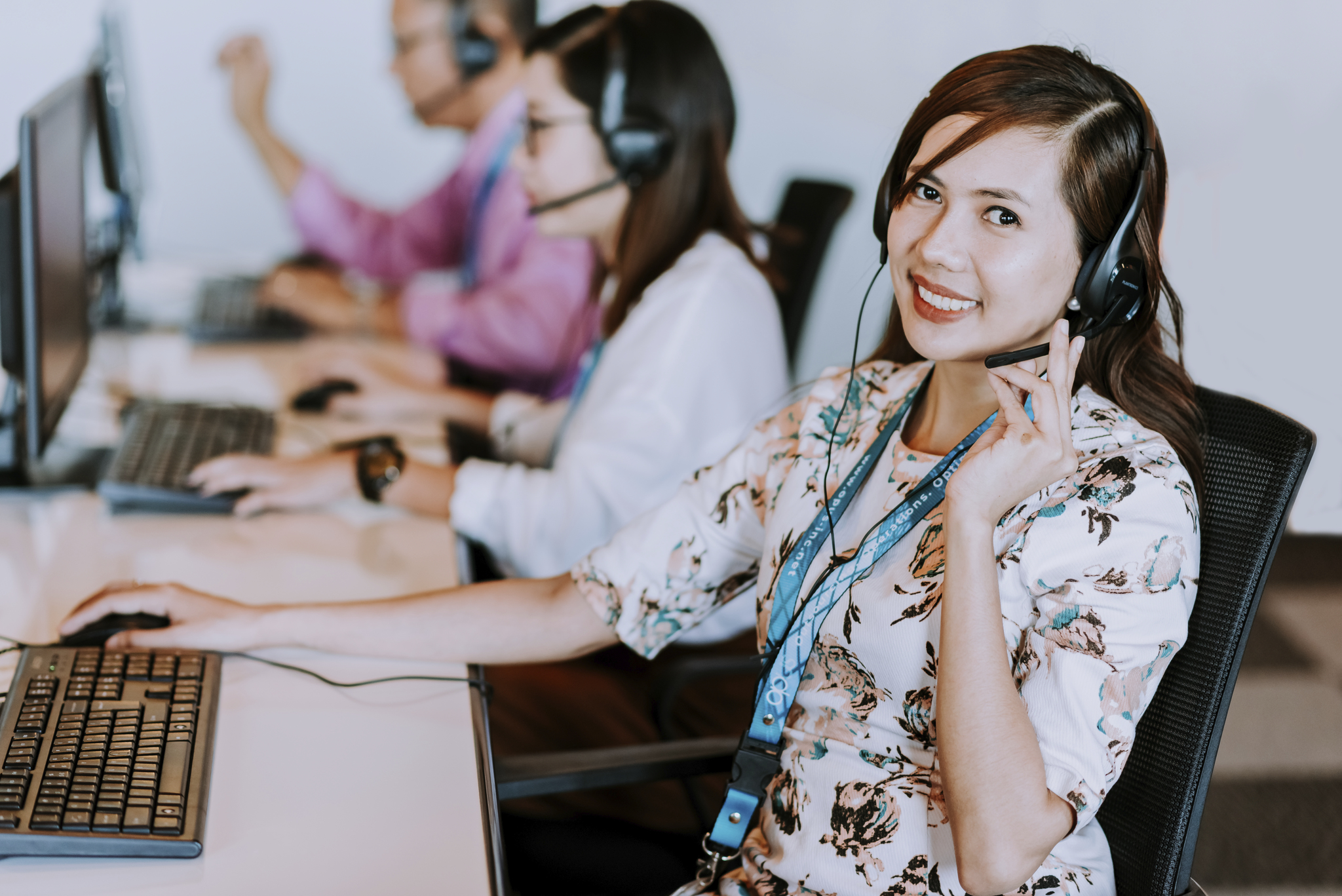 Smiling Female call center agent holding her headset with a headset