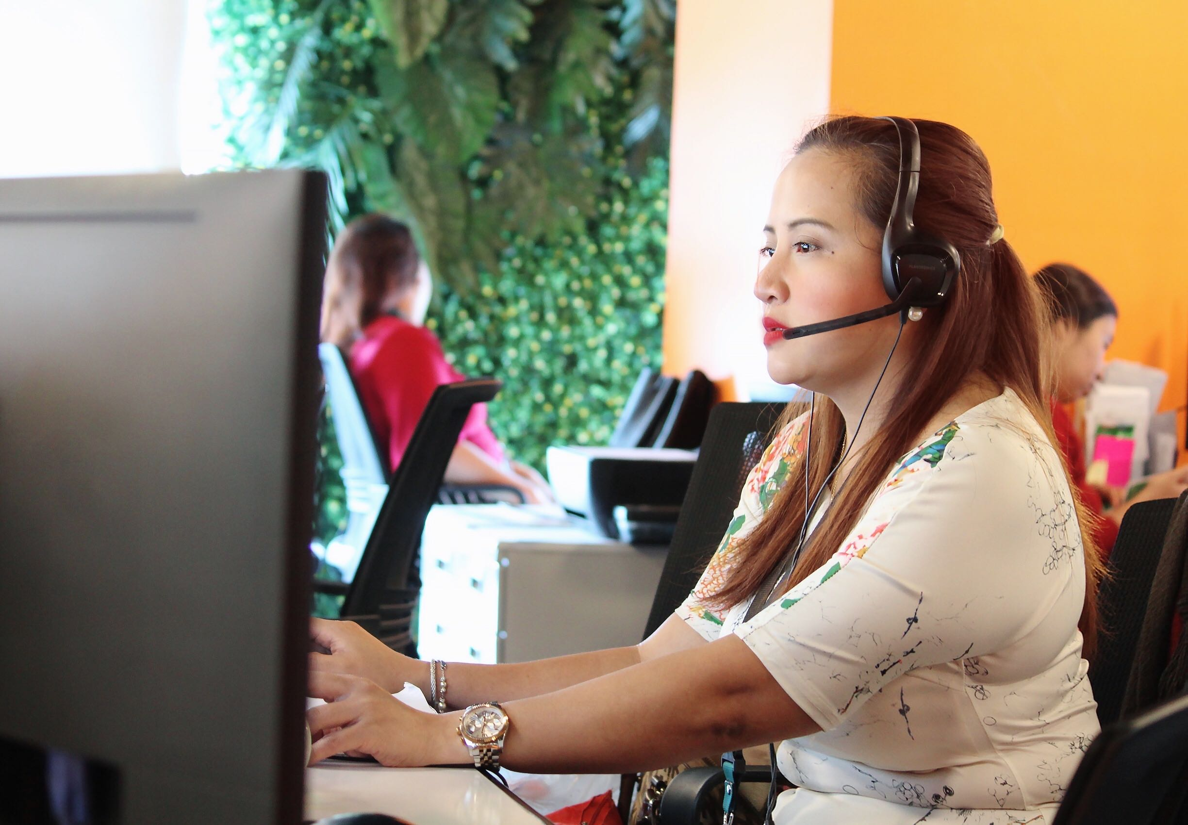 woman working as a remote staff Virtual Assistant orange