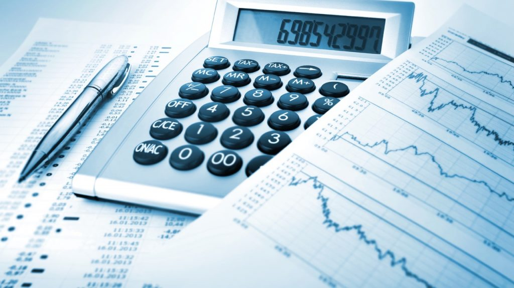 A calculator, pen and financial assets sheet for Finance Outsourcing professionals